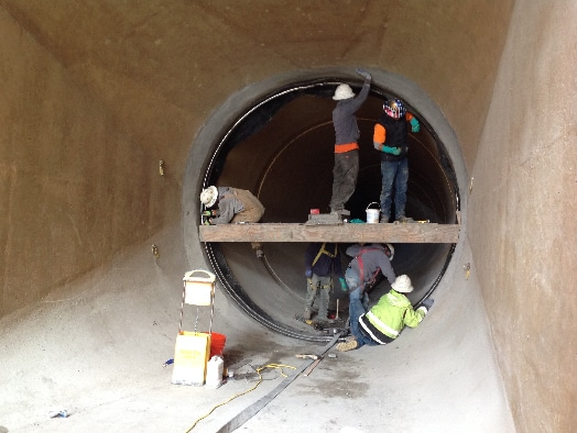 A HydraTite Seal being installed by multiple Field Services Technicians in a large diameter pipe