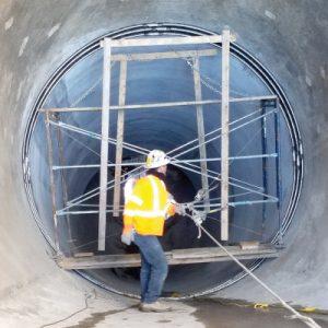 Field Technician Inspecting a seal in a 13ft-Diameter Concrete Pipe