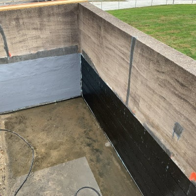two conjoined concrete walls partially wrapped in HydraWrap for protection